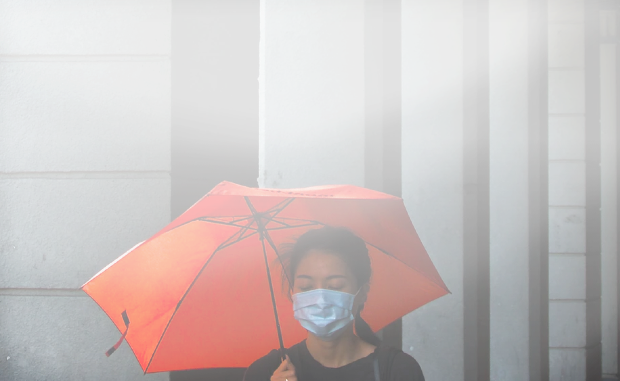 A woman wearing a face mask and carrying a red umbrella walks down a rainy street, while looking at her phone
