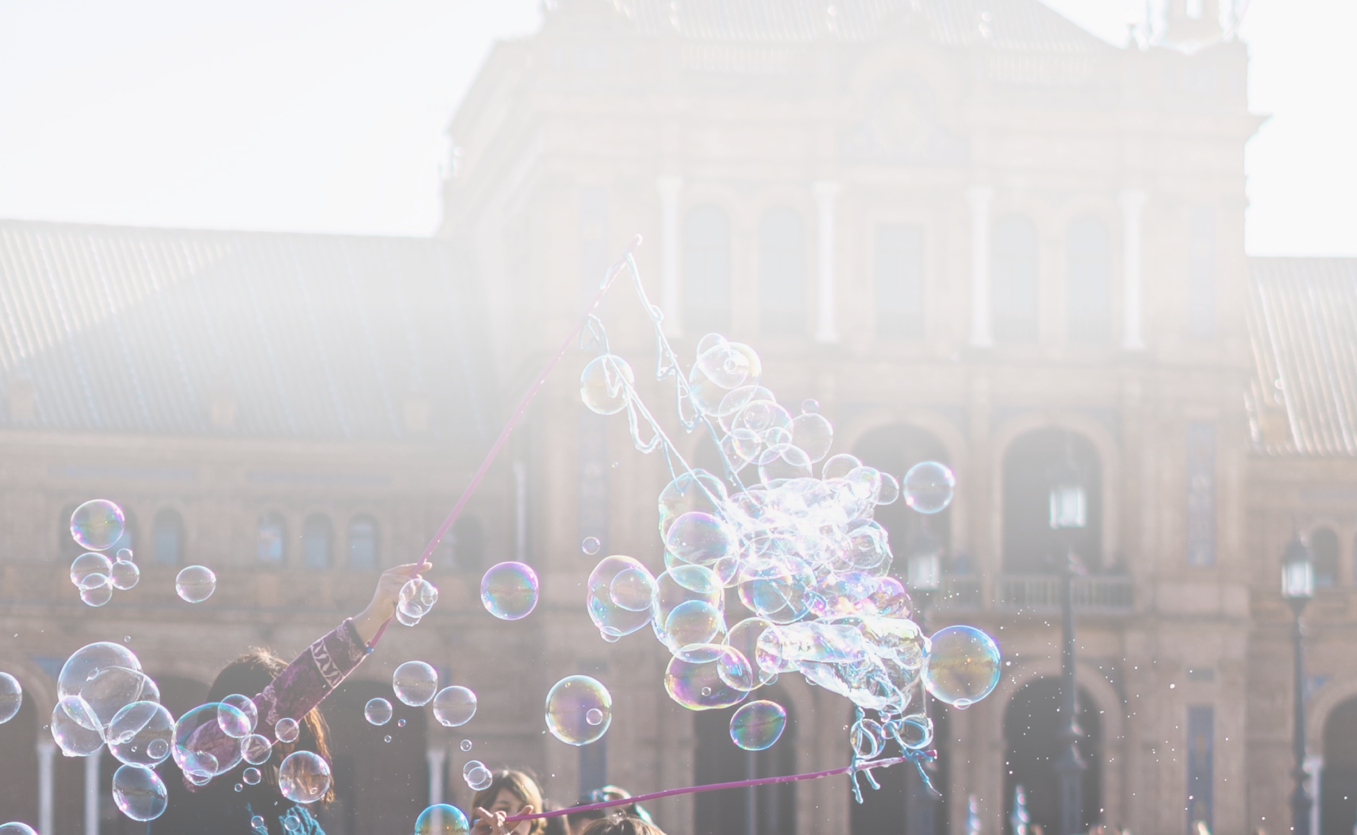 A man blows bubbles for a group of children in a city square